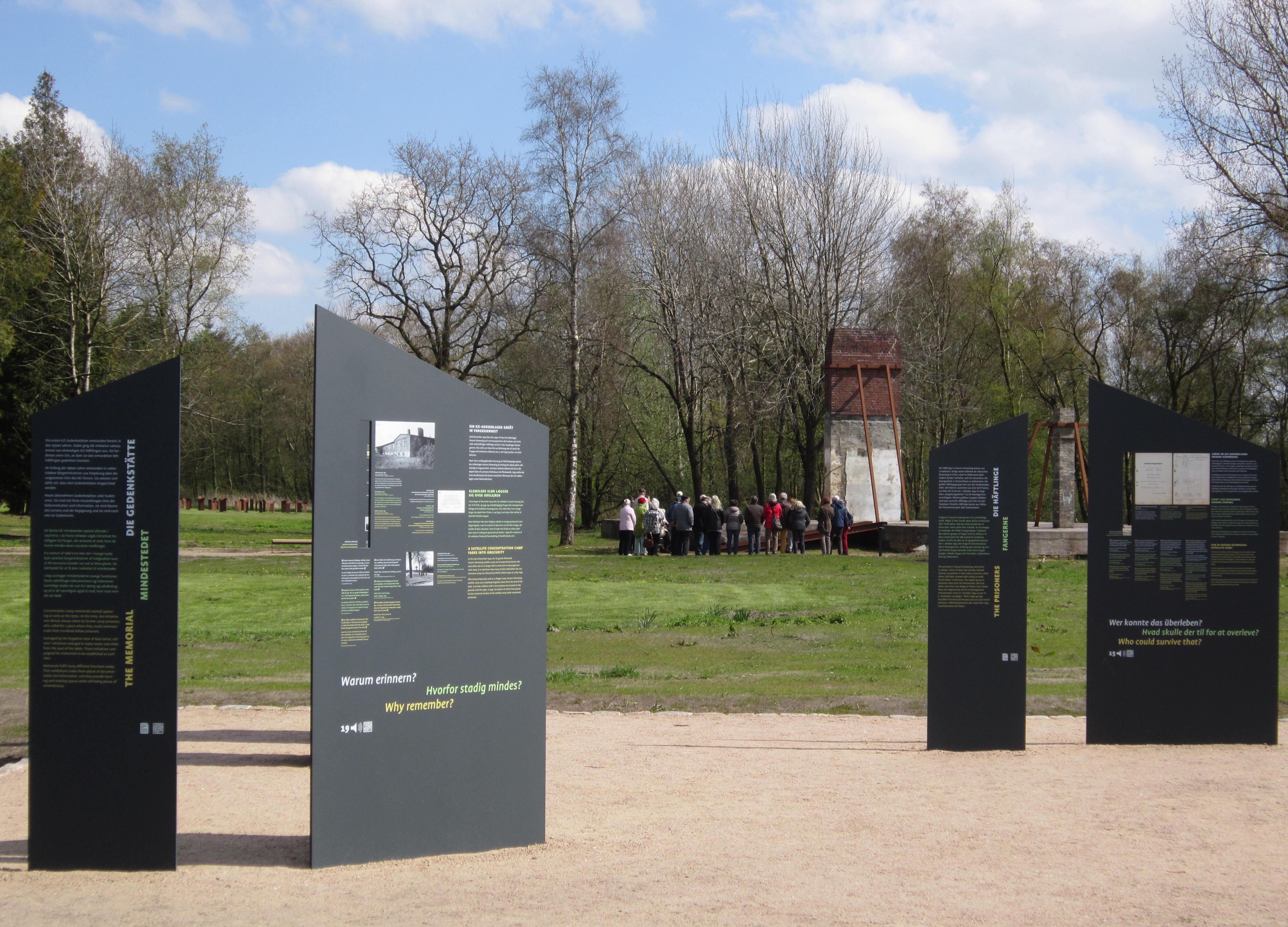 Die im April 2017 eingeweihte Außenausstellung der KZ-Gedenkstätte Husum-Schwesing. Im Hintergrund steht eine geführte Gruppe an den Überresten der Küchenbaracke. 30. April 2017